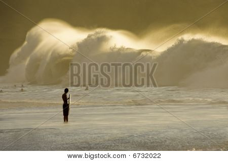 Big wave breaking on the shore and the silhouette of one bodyboarder watching it in the evening. Waimea Bay in the North Shore of Oahu. Hawaii. poster
