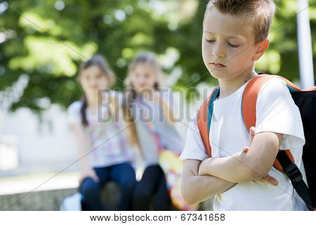 Two little girls poting at the little sad boy, focus on foreground