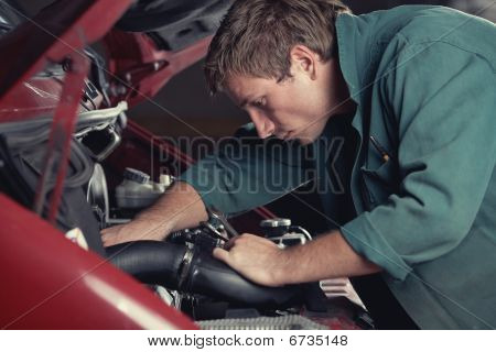 Mechanic at work fixing car in auto service poster