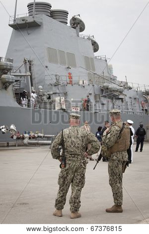 STATEN ISLAND, NY - MAY 21, 2014: Armed U.S. Navy personnel patrol Sullivans Piers while the guided-missile destroyer USS Cole (DDG 067) is docked during Fleet Week NY on May 21, 2014.
