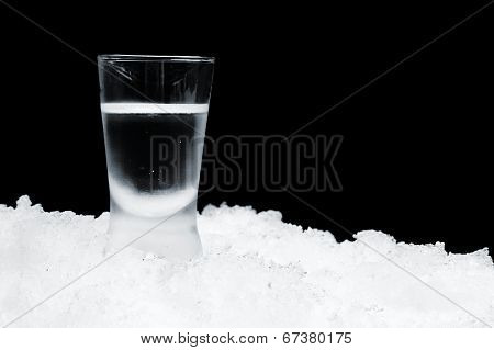 Glass Of Vodka Standing On Ice On Black Background