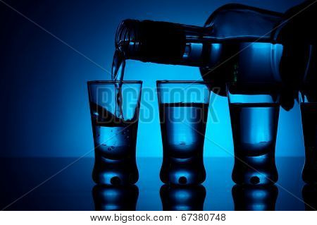 Vodka Poured Into A Glass With Glasses Lit With Blue Backlight