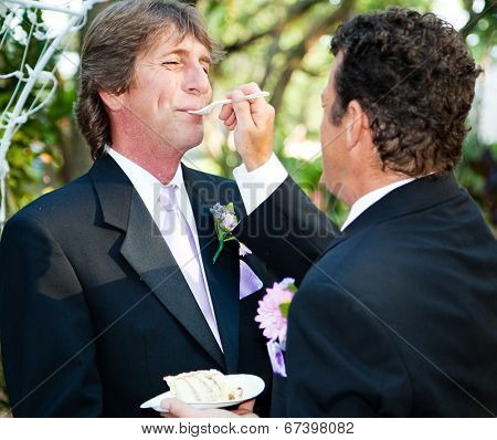 One groom feeds another wedding cake at their gay marriage ceremony.