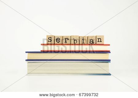 serbian word on wood stamps stack on books foreign language and translation concept poster