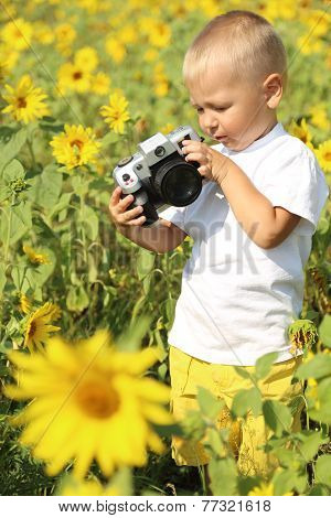 kid with the camera in a field of sunflowers