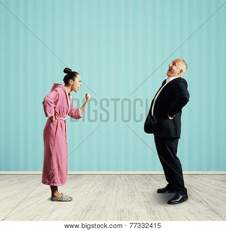 emotional woman in pink dressing gown screaming and showing fist laughing senior man in suit