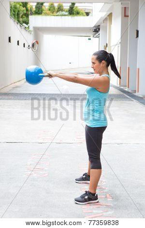 Beautiful hispanic sport woman swing the blue kettlebell, outdoor