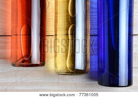 High angle shot of  red, white, and blue wine bottles on a rustic white wood table. The bottles have no labels. Horizontal format.