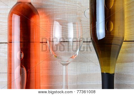 Closeup of a wine glass between a bottle of red wine and a bottle of white wine. All three objects are laying on a rustic white wood table. Horizontal format from a high angle.