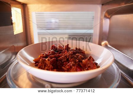 Leftover Chili Cooking Inside Microwave Oven poster
