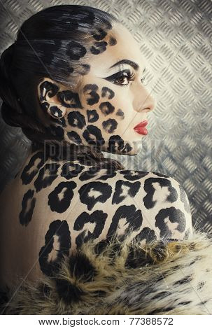 young sexy woman with leopard make up all over body, cat bodyart closeup