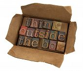think outside the box concept words in vintage letterpress type in open cardboard box isolated on white poster