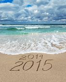 Happy New Year 2015 wash away year 2014 concept on sea sand beach poster