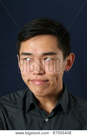Young Asian man making face and rolling eyes up