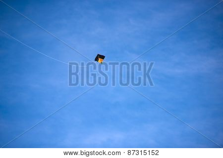 A bright colored kite soaring against the blue sky