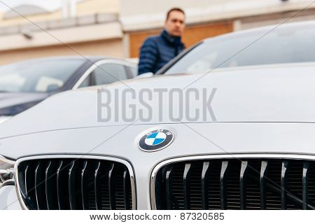 Man Looking At Bmw Car Before Making Decision To Buy It
