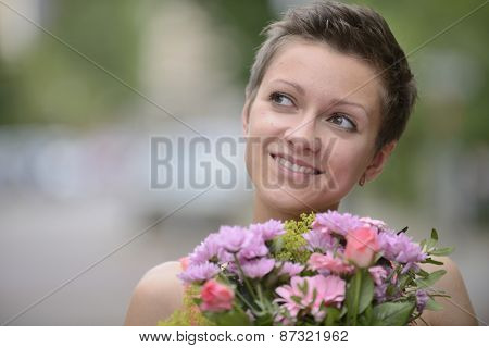 Happy woman holding bunch of flowers in spring