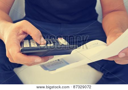 closeup of a young man checking a bill, a budget or a payroll with a calculator, filtered effect