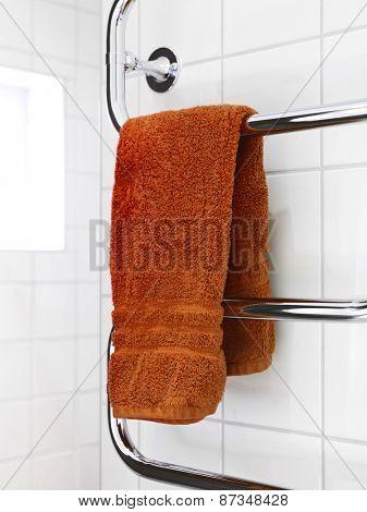 Orange Towel on a dryer in modern bathroom environment