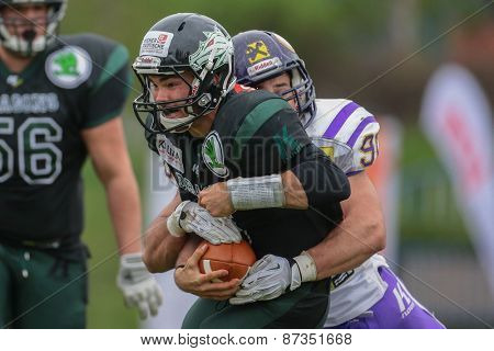 VIENNA, AUSTRIA - APRIL 13, 2014: QB Cary Grossart (#5 Dragons) is tackled by DL Alexander Taheri (#90 Vikings).
