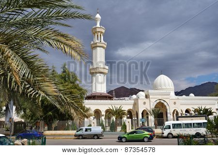 AQABA, JORDAN - MARCH 14, 2014: People near the Al Sharif Hussein Bin Ali mosque in a springtime day. The mosque was built in 1975 and in 2011 was renovated and enlarged