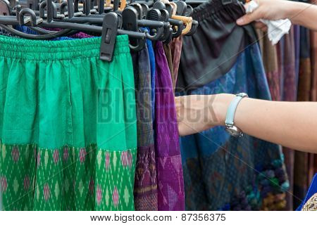 sale, retail, shopping and clothing concept - close up of hands choosing skirts at street market poster