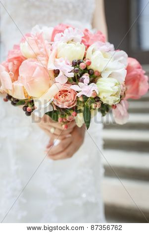 Beautiful wedding bouquet of pink and white peony flowers in hands of the bride