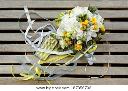 wedding photo set in yellow and gray colours: rings, telephone case and bouquet of roses, Craspedia, Hydrangea, Brunia silver flowers
