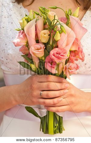 Beautiful wedding bouquet of calla and eustoma flowers in hands of the bride