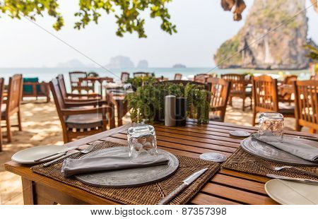 leisure, travel and tourism concept - close up of table setting at open-air restaurant on beach