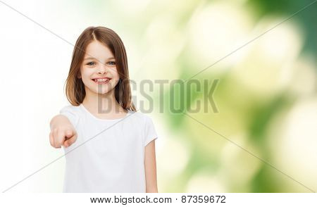 advertising, childhood, gesture, ecology and people - smiling little girl in white blank t-shirt pointing finger on you over green background