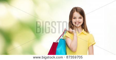 shopping, happiness and people concept - smiling little girl in yellow dress with shopping bags