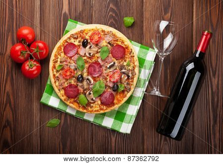 Italian pizza with pepperoni and red wine on wooden table. Top view