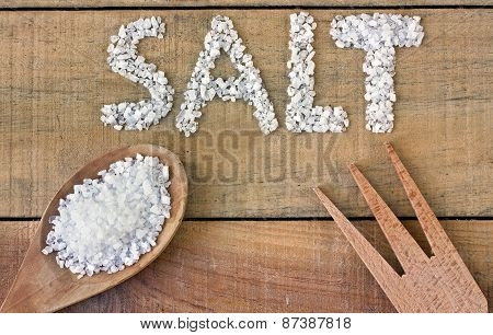 Salt In Spoon On A Wooden Table