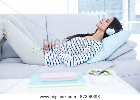 Smiling beautiful brunette relaxing on the couch and listening music in the living room poster
