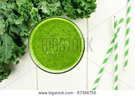 Green kale smoothie on white wood
