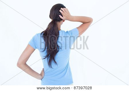 Thoughtful brunette scratching head on white background