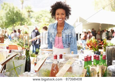 Woman Selling Soft Drinks At Farmers Market Stall