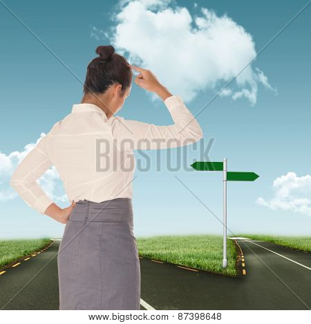Businesswoman scratching her head against road leading out to the horizon