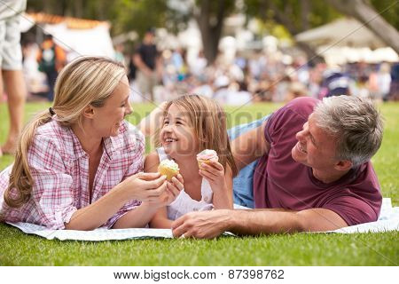 Family Enjoying Cupcakes At Outdoor Summer Event