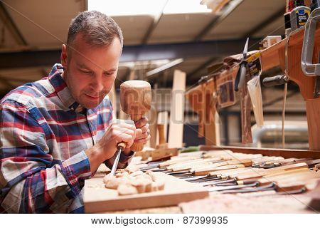 Carpenter Carving Wood Using Chisel