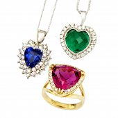 Combination of Three Jewellery Pieces: Heart Shaped Sapphire and Diamond Pendent, Heart Shaped Emerald and Diamond Pendent, and a Ruby and Diamond Ring, Isolated on White Background poster