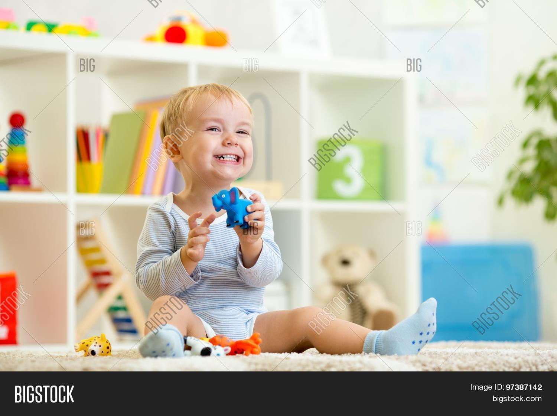b5b4a2632 happy child boy holds elefant toy sitting on floor in nursery