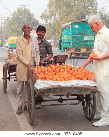man sells oranges on the market in Delhi, India