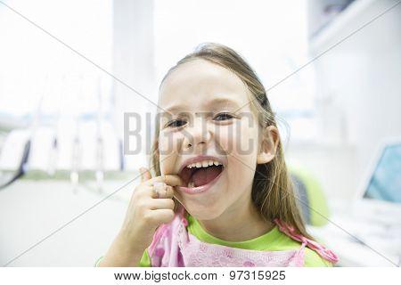 Girl Showing Her Healthy Milk Teeth At Dental Office