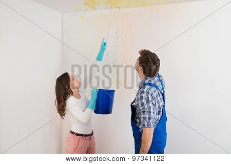 Young Woman With Bucket Showing Water Leaking From Damage Ceiling To Maintenance Guy poster