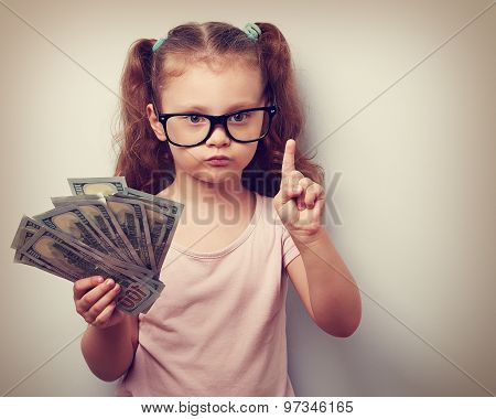 Cute Kid Girl Holding Dollars And Have An Idea How Earning Much Money In Crisis. Serious Child In Ey