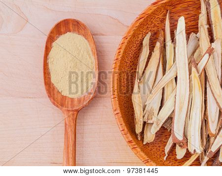 Licorice Herbal Medicine In Wooden Spoon, Chopped And Sliced On Wooden Table