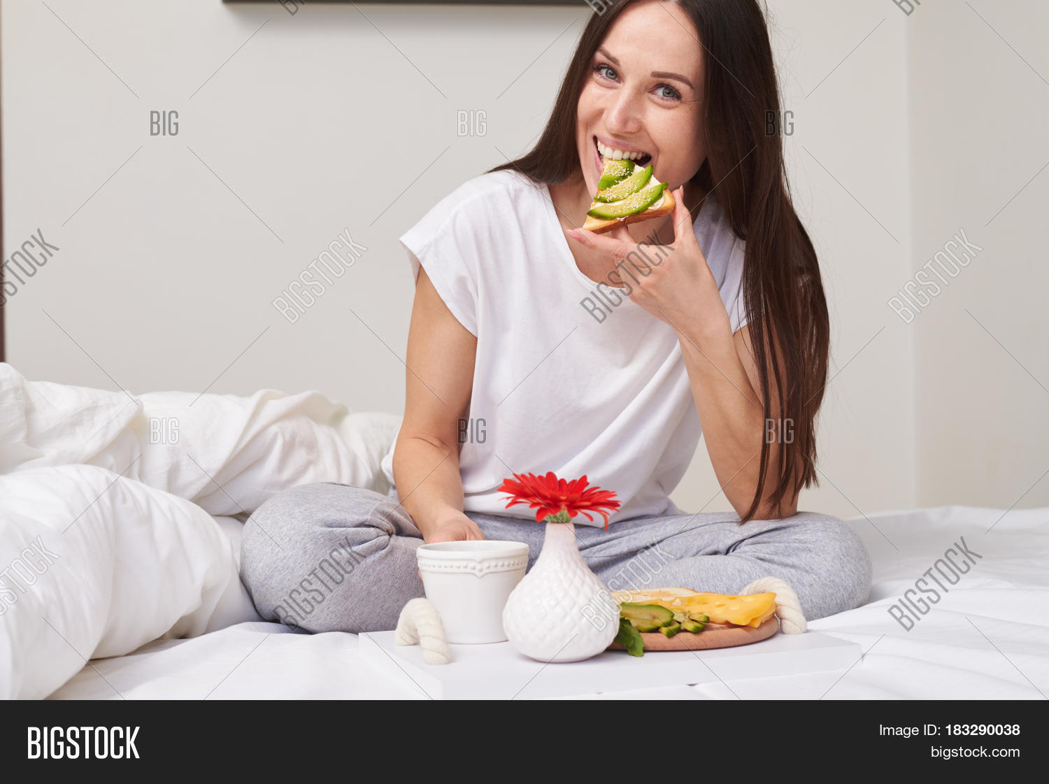 Mid shot of smiling woman in pajamas eating sandwich and enjoying romantic breakfast sitting in the bed with copy space