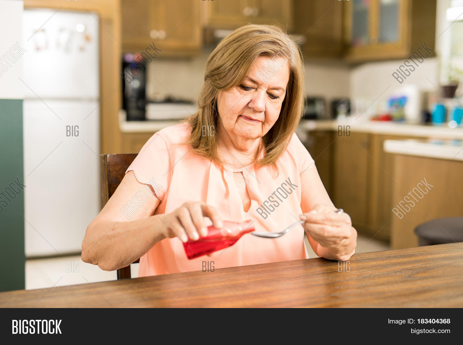 mature mom filling spoon syrup image & photo | bigstock